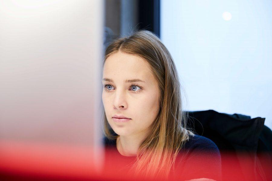 Grafikerin Anna Fischerlehner konzentriert von dem Bildschirm