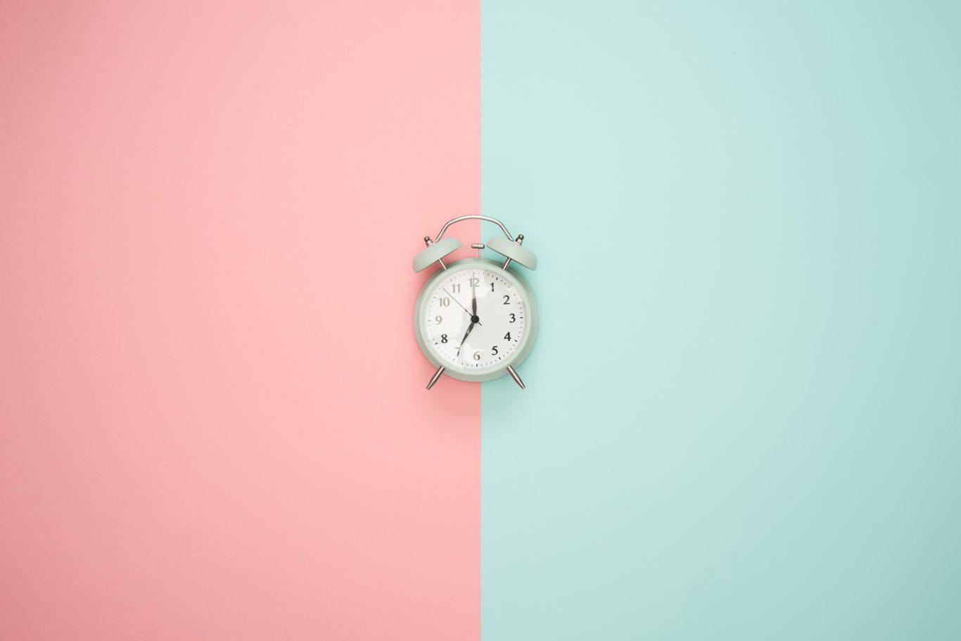 Zeit haben: Wecker auf Hintergrund rose und türkis
