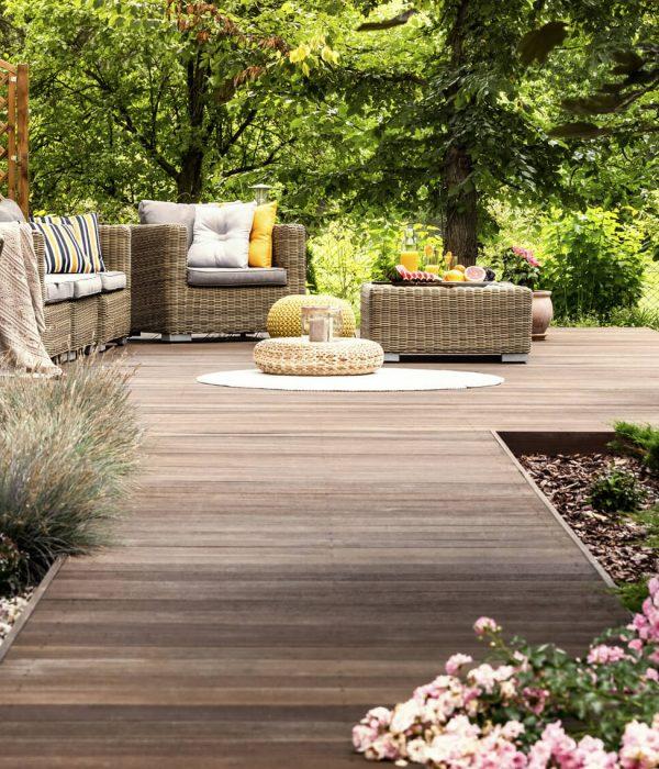 Holzweg mit Hängesessel und Sitzgarnitur im Garten